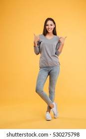 Full length happy model in studio. shows fingers up. isolated orange background