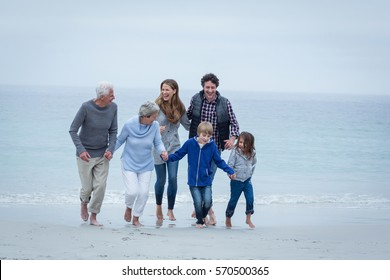Full length of happy multi-generation family enjoying at sea shore against sky