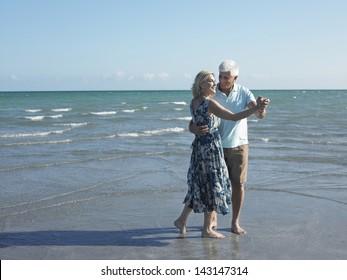 Full length of happy senior couple dancing on tropical beach
