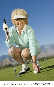 Full length of a happy senior woman playing golf