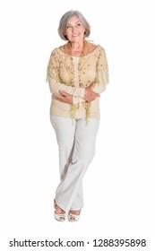 Full length, happy senior woman posing on white