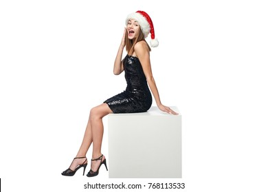 Full length happy surprised Christmas girl in sequined dress and Santa sitting on big white box with blank copy space