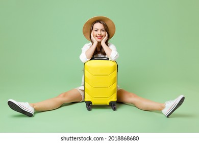 Full length happy traveler tourist woman in casual clothes hat sitting with outstretched legs near suitcase isolated on green background Passenger travel abroad weekends Air flight journey concept.