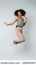 Full length of a happy young african woman casually dressed jumping isolated over gray background