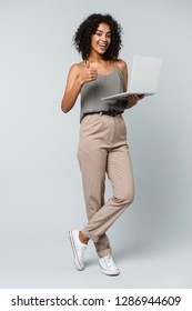 Full length of a happy young african woman casually dressed standing isolated over gray background, working on laptop computer