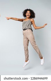 Full length of a happy young african woman casually dressed jumping isolated over gray background, pointing at copy space