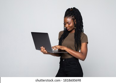 Full length of a happy young african woman standing isolated over gray background, working on laptop computer
