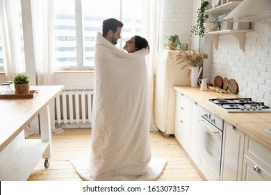 Full length happy young family couple standing in kitchen, covered in blanket, enjoying romantic weekend time together. Smiling loving married spouse embracing cuddling hugging, spending holiday.