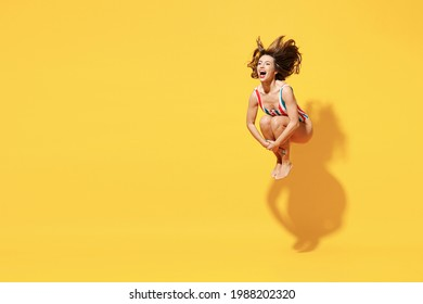 Full length happy young sexy woman slim body wear striped red blue one-piece swimsuit jump dive into water isolated on vivid yellow color background studio. Summer hotel pool sea rest sun tan concept