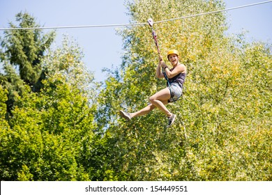 Full length of happy young woman hanging on zip line against trees in forest