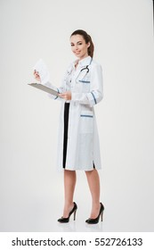 Full length of happy young woman doctor holding clipboard with documents over white background