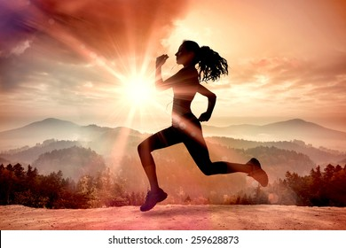 Full length of healthy woman jogging against misty landscape