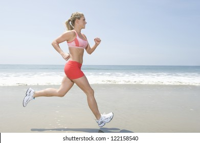 Full length of healthy young woman jogging on seashore