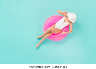 Full length high angle top above view photo of gentle lady bronze skin sitting swimming pool big life buoy wear sun hat white swim bodysuit isolated pastel teal color background