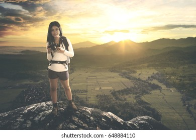 Full length of hiker female holding a digital camera while standing with beautiful rice field landscape