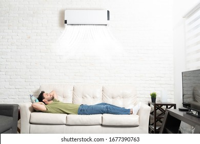 Full length of Hispanic man sleeping below mini split on sofa in living room at home