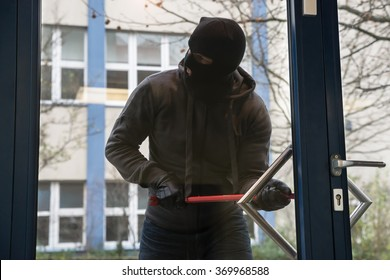 Full length of hooded man using crowbar to open glass door