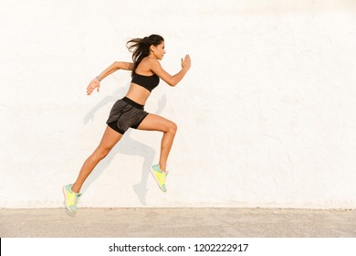 Full length image of athletic woman 20s in sportswear working out and running along wall
