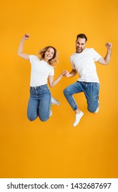 Full length image of attractive couple rejoicing and jumping while clenching fists together isolated over yellow background