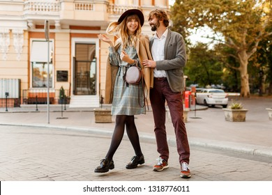 Full length Image of  beautiful fashionable couple in love walking in sunny spring city while dating. Enjoying honeymoon in European city.