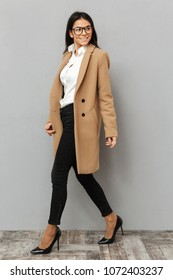 Full length image of beautiful woman wearing glasses and beige coat walking on heels and looking aside with smile isolated over gray background