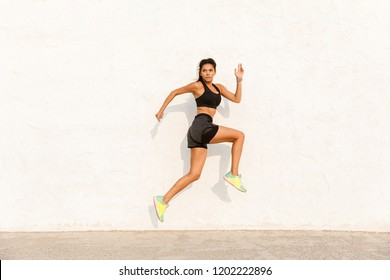 Full length image of beautiful woman 20s in sportswear working out and running along wall