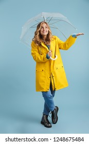 Full length image of blonde woman 20s wearing yellow raincoat standing under transparent umbrella isolated over blue background