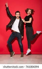 Full length image of carefree screaming punk couple posing and looking at the camera over red background