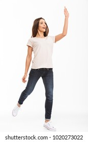 Full length image of Cheerful brunette woman in t-shirt walking while waving and looking away over white background