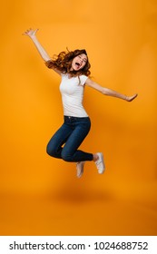 Full length image of Cheerful brunette woman in t-shirt jumping and rejoices with closed eyes over yellow background