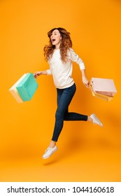 Full length image of Cheerful brunette woman in sweater running with packages over yellow background