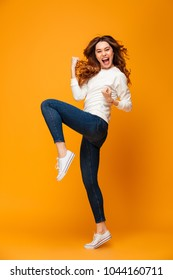 Full length image of Cheerful brunette woman in sweater rejoices and looking at the camera over yellow background