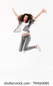 Full length image of Cheerful curly woman jumping in studio and looking away over white background