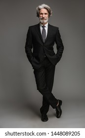 Full length image of confident adult businessman wearing formal black suit standing at camera with hands in pockets isolated over gray background