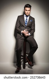 Full length image of a elegant business man holding his hands while sitting on a stool, looking at the camera and thinking.