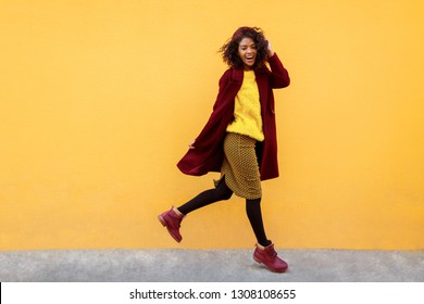 Full length image of excited black woman jumping with happy face expression on yellow background.