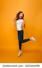 Full length image of Happy brunette woman in t-shirt jumping while looking and pointing away with thumbs over yellow background