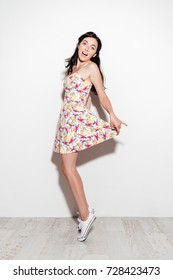 Full length image of happy brunette woman in dress dancing in studio and looking at the camera over white background