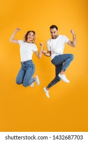 Full length image of happy couple rejoicing and jumping while clenching fists together isolated over yellow background