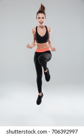 Full length image of happy fitness woman over gray background