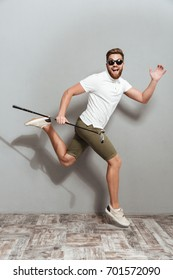 Full length image of a Happy funny golfer in sunglasses with club in hand over gray background