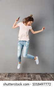 Full length image of Happy woman in t-shirt listening music from smartphone with earphones while jumping and looking down over grey background