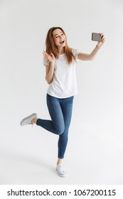 Full length image of Happy woman in casual clothes posing and making selfie on smartphone while waving at camera over grey background