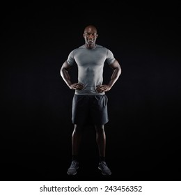 Full length image of happy young man standing on black background. Muscular african athlete in sportswear.