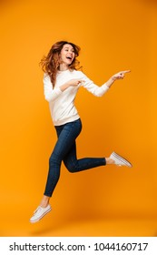 Full length image of Joyful brunette woman in sweater running while pointing and looking away over yellow background