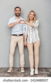 Full length image of nice couple in casual clothing smiling and showing heart shape with fingers isolated over gray background