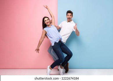 Full length image of optimistic man and woman in casual wear laughing and having fun together isolated over colorful background