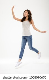 Full length image of Pleased brunette woman jumping and waving away over gray background