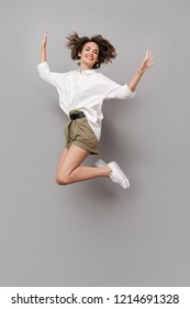 Full length image of positive girl 20s smiling and jumping isolated over gray background