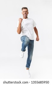 Full length image of positive man 30s wearing casual t-shirt and jeans clenching fists isolated over white background